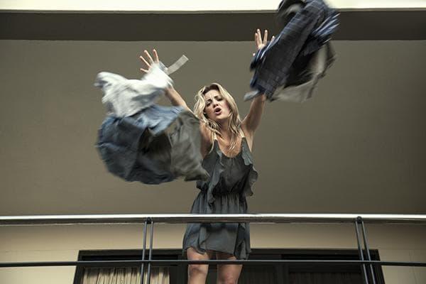 Женщина выбрасывает вещи с балкона