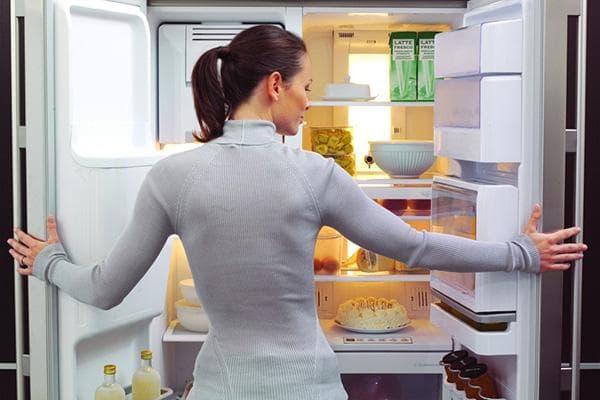 Женщина у холодильника с продуктами