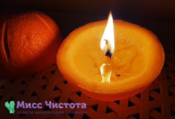 Зажженная свеча из кожуры апельсина