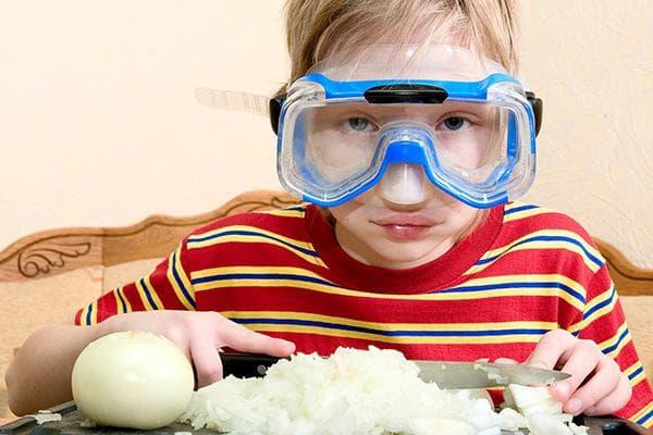 Мальчик режет лук в очках для плавания