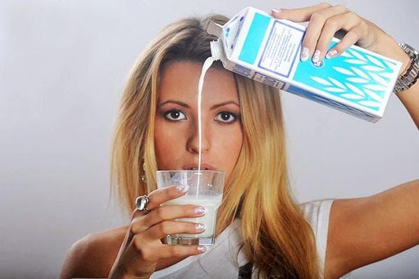 Девушка наливает молоко в стакан