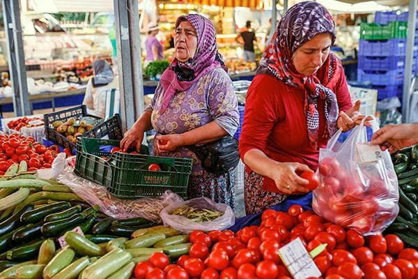Женщины на рынке продают томаты