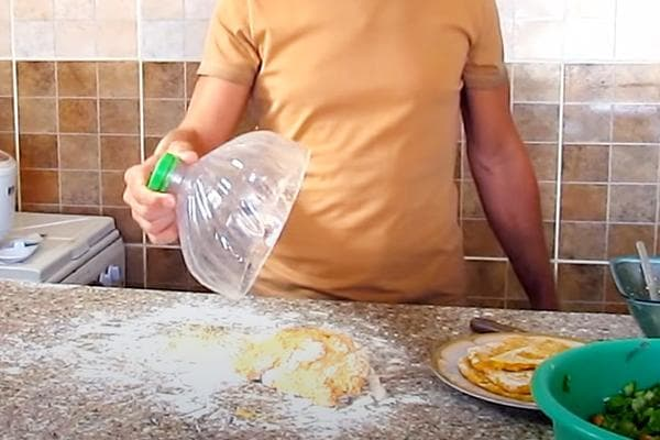 Мужчина накрывает тесто верхушкой от пластиковой баклажки