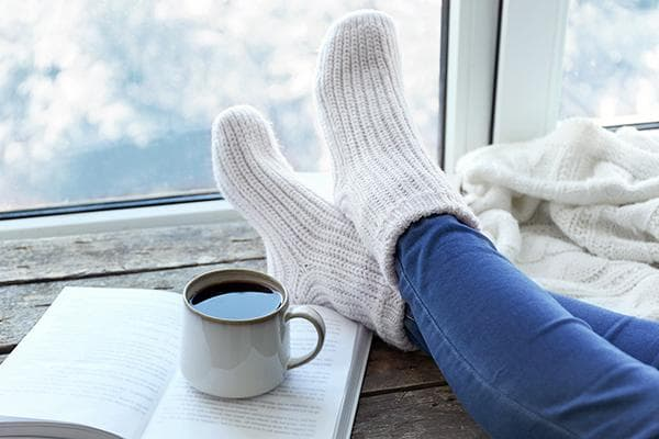 Шерстяные носки и кружка с чаем