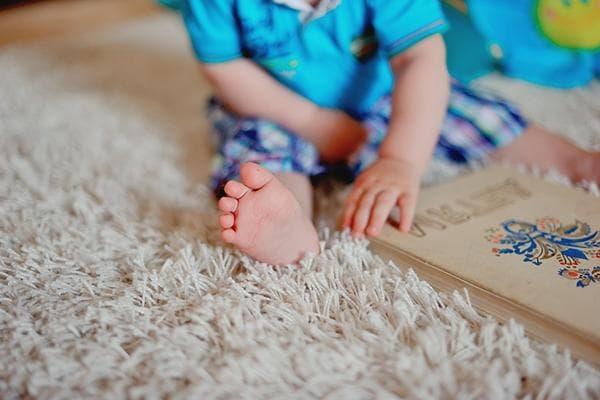 Ребенок сидит на ковре с длинным ворсом