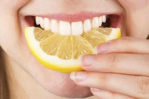 Девушка кусает дольку лимона